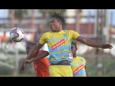 Waterhouse's goalscorer Stephen Williams (front) battles Tivoli Gardens' Trayvon Reid for possession during their Red Stripe Premier League game at the Edward Seaga Complex yesterday.