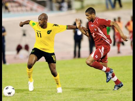 Shelton (left) holds off a Panama opponent during a friendly international football match at the National Stadium in Kingston in June 2009.